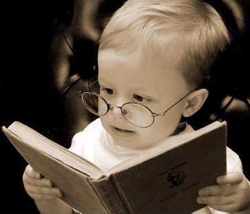 Small boy reading a book (taken from bookriot.com)